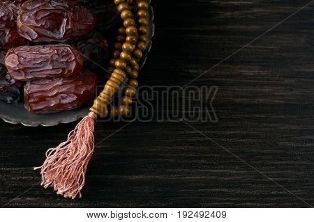 Top view of Dates for iftar and prayer rosary on black wooden table. Copy space. Islamic religion and ramadan month concept.