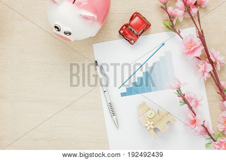 Top view business office desk concept. Saving money with charted summary Wood house also car and clock on wooden shelf.The beautiful pink flower with pen on wood background with copy space.