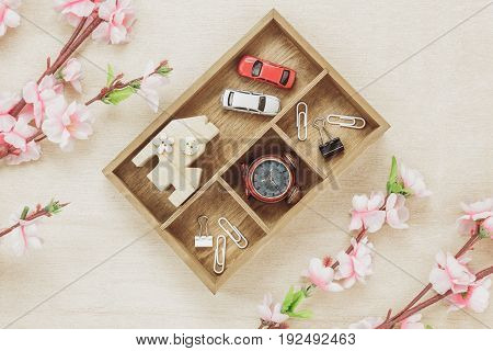 Top view business office desk concept. Wood house also car and clock on wooden shelf.The beautiful pink flower on wood background with copy space.