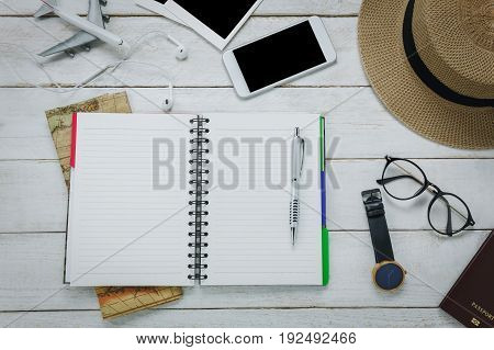Top view accessoires to travel concept.Notebook free space for writing with pen on white table backgroun.Items is mapwatcheyeglassespassporthatmobilephoneairplaneeyephonephoto.