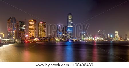 Shanghai, China - Nov 4, 2016: Shanghai City skyline by night. Features the shoreline and Huangpu River. Long exposure, available-light image. Some low-lying fog moving in.