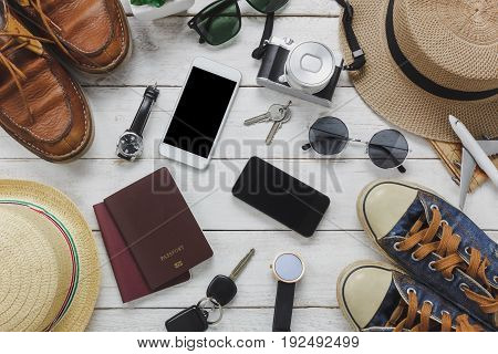 Top view women and man accessoires to travel concept.White and black mobile phone airplane hat passport watch sunglasses shoes and key on wood table.
