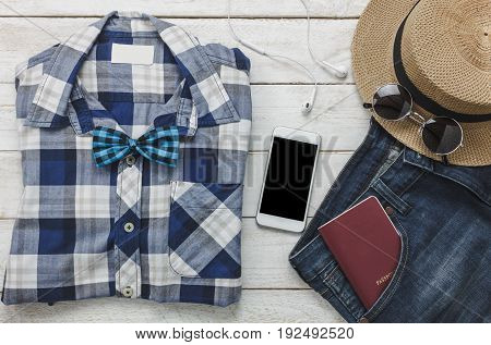 Top view accessoires to travel with man clothing concept. shirt jean mobile phone listening music by headphone on wooden background.passport key sunglasses and hat on wood table.