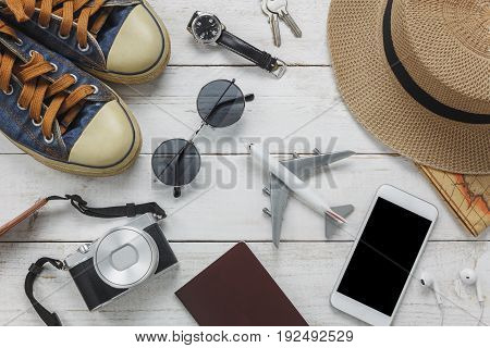 Top view women accessories to travel concept.White mobile phone and headphone on wooden background.airplanehatpassportwatchsunglasses on wood table.