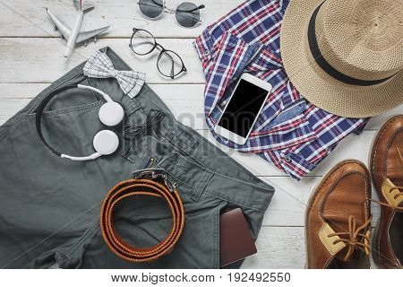 Top view accessoires to travel with man clothing concept. shirt jean mobile phone headphone on wooden background.passportkeyeyeglasses and shoes on wood table.