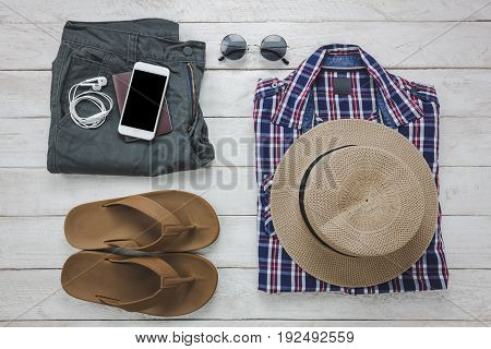 Top view accessoires to travel with man clothing concept. shirt jean mobile phone headphone on wooden background.passportkeyeyeglasses and slipper on wood table.