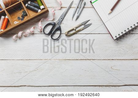Top view accessories tailor concept.Tailor tools is cutting scissors spools of thread tape measurement buttons and sewing clothes. Notebook for free space text on rustic wooden background.