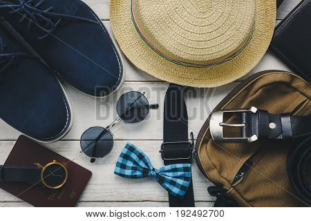 Top view accessories to travel with man clothing concept. bow tie wallet on wooden background. watch sun glasses bag hat and shoes on wood table.