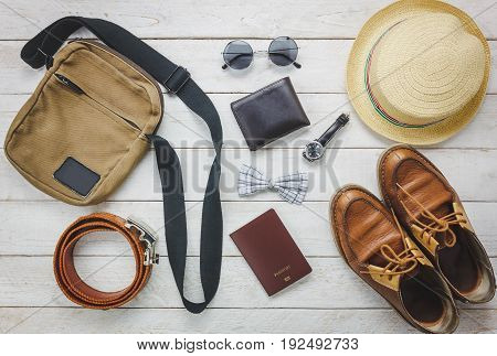 Top view accessories to travel with man clothing concept. bow tie wallet on wooden background. watch sunglasses bag hat belt and shoes on wood table.