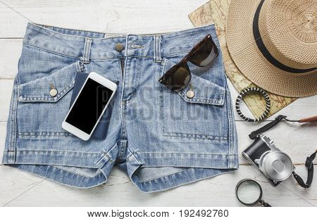 Top view accessories to travel with women clothing concept.White mobile phone hat map camera necklace trousers and sunglasses on white wood table.