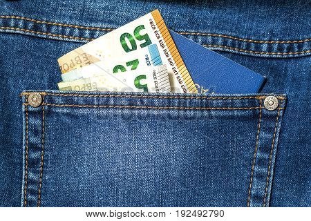 Euro money banknotes and travel passport in a pocket of blue jeans close up