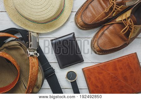 Top view accessoires to travel with man clothing concept. wallet on wooden background.watchbaghatnotebook and shoe on white wood table.