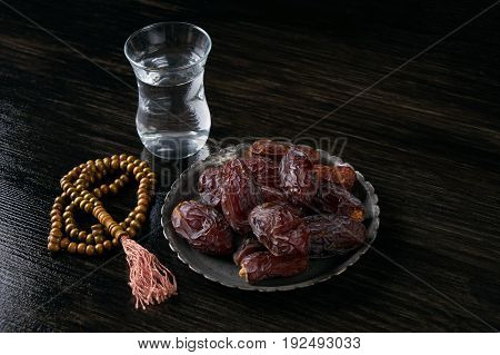 Ramadan ramazan kareem. Glass of water and dry dates for iftar party holidays on black wooden table. Copy space background.