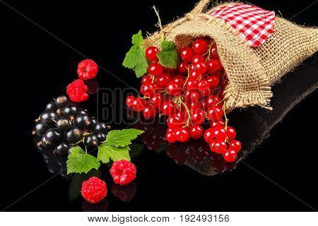 Fruits of raspberry, black currant and red currant on a dark background. Close-up
