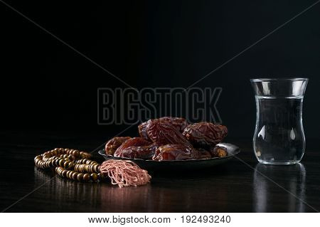 Ramadan ramazan kareem. Glass of water and dry dates for iftar party holidays on black wooden table isolated on black background with copy space.