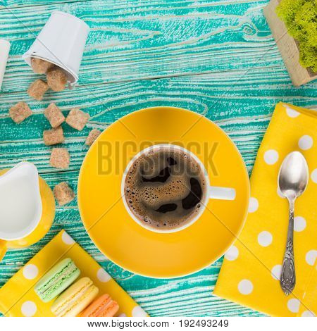 cup ofcoffee on yellow plate and yellow milk jug cane sugar macaroons teaspoon on yellow napkin at polka dots on turquoise colored wooden table top view