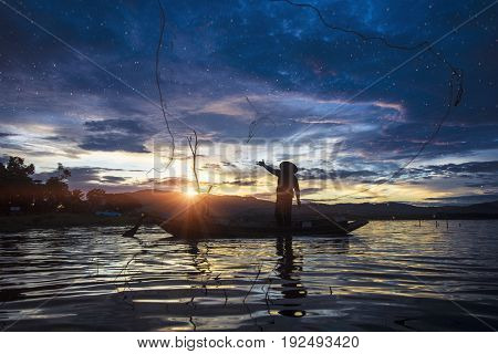 Silhouette Fisherman Fishing by using Net on the boat in Thailand