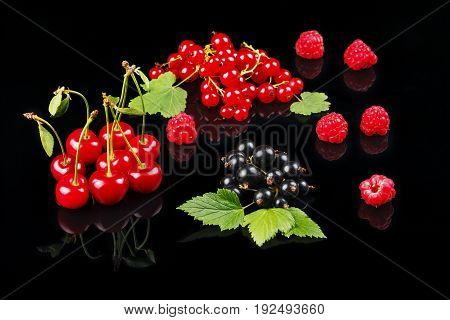 Fruits of cherry, raspberry, black currant and red currant on a dark background. Close-up
