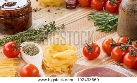 cherry tomatoes dried tomatoes in glass jar on wooden table Parmesan basil leaf thyme rosemary prosciutto pasta spaghetti olive oil in clay jug italian food concept