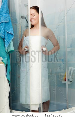 Girl showering in shower cabin cubicle enclosure. Young woman with white towel taking care of hygiene in bathroom. poster