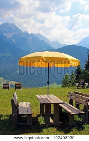 benches and a table with a yellow parasol and a georgeous view to the Austrian mountainis in the region Hochkoenig