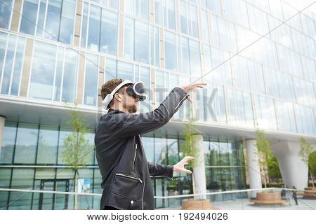 Outdoor shot of fashionable European man with beard wearing 3d glasses holding hands as if grasping something or interacting with someone. Young male using virtual reality headset on street