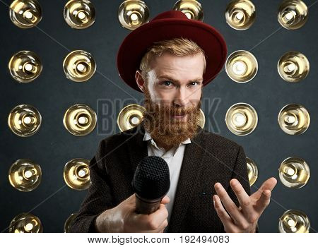 Horizontal shot of handsome bearded performer or showman wearing stylish red hat and suit performing in front of audience singing or speaking into microphone standing over wall with round lamps