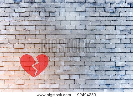 Broken heart breakup concept. Red heart broken sad separation on the brick wall background.