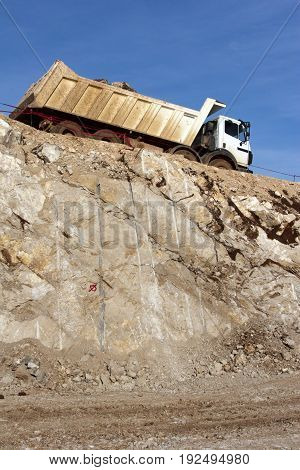 Heavy truck transports material on construction site of highway