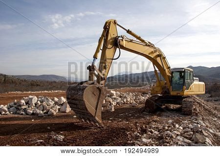 Yellow backhoe working on construction of road
