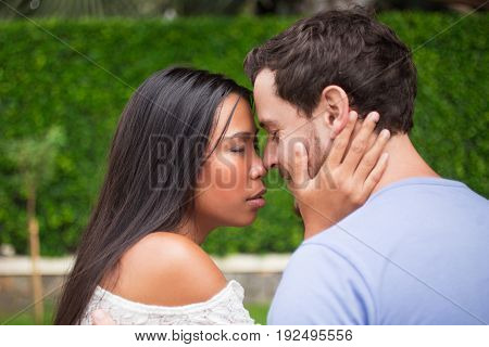 Closeup of affectionate young interracial couple touching noses and hugging with their eyes closed and blurred green leaves wall in background. Woman embracing boyfriend neck. Side view.