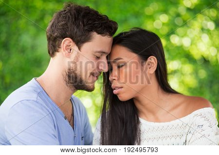 Closeup of affectionate young interracial couple touching foreheads with their eyes closed and blurred green leaves wall in background