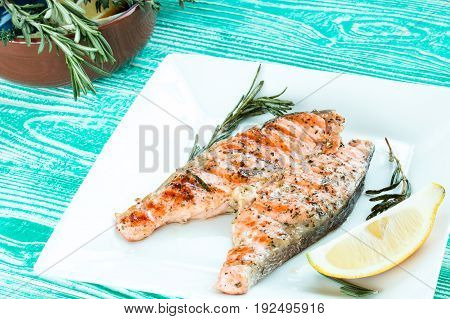Grilled steak of salmon with rosemary and lemon in square plate on turquoise colored wooden table