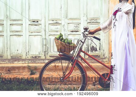 Beautiful women Vietnam with white Ao Dai dress and red bicycle in old city selective and soft focus of face color vintage style
