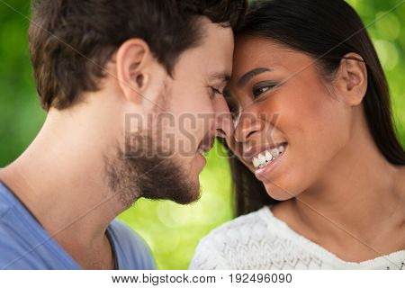 Closeup portrait of smiling young interracial couple touching foreheads