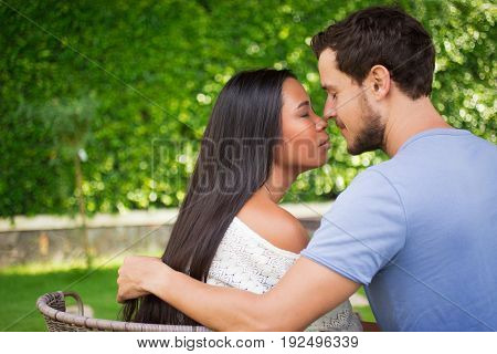 Closeup of affectionate young interracial couple touching noses and hugging with their eyes closed and blurred green leaves wall in background. Side view.