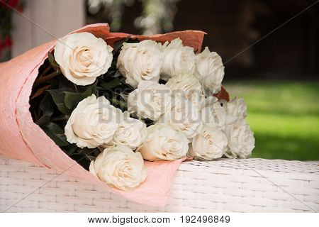 a bouquet of white roses lies on a wicker table