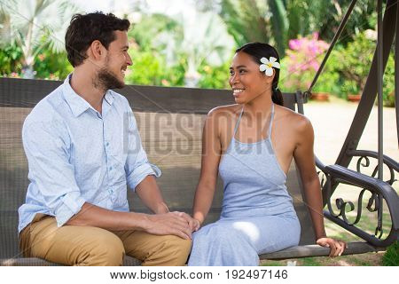 Closeup portrait of smiling young Caucasian man and his Asian girlfriend looking at each other and sitting on swinging bench with blurred plants in background