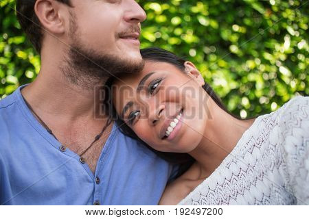 Closeup of smiling young Asian woman leaning head on Caucasian boyfriend shoulder with green leaves wall in background. Cropped view.
