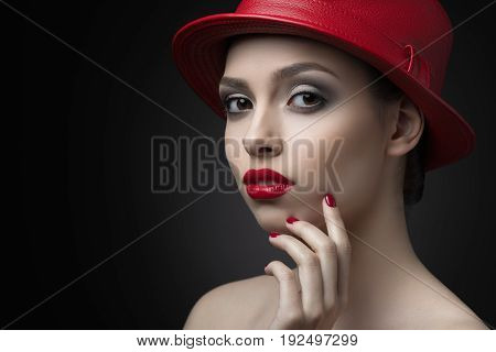 Young brunette girl with red lips, red manicure and in a red hat