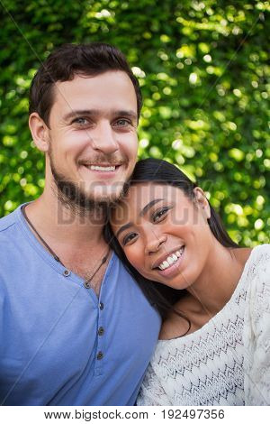 Closeup of smiling young Asian woman leaning head on Caucasian boyfriend shoulder with green leaves wall in background. They are looking at camera.