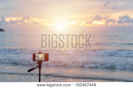 Someone travel at Patong beach Phuket Thailand keep mobile phone on tripot wait time sunset for good photo. selective focus on mobile phone and soft focus the sea and sky