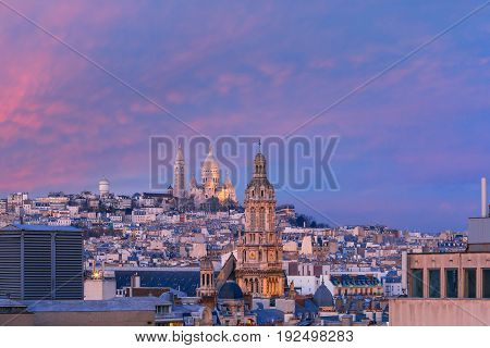 Aerial view of Sacre-Coeur Basilica or Basilica of the Sacred Heart of Jesus at the butte Montmartre and Saint Trinity church at nice sunset, Paris, France