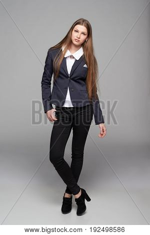 Full length stylish teen girl in black pants and jacket, over grey background