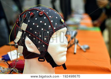 The electroencephalogram (EEG) head cap with flat metal discs (electrodes) attached to a white plastic model's head shown in a science exhibition with laptops blurred at the background. EEG is widely used in brain science research.