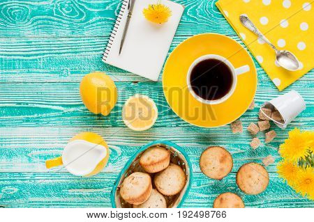 cup of black tea on yellow plate and yellow milk jug cane sugar notebook pen cakes dandelions teaspoon on turquoise colored wooden table with yellow napkin at polka dots top view