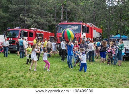 Zaporizhia/Ukraine- May 28, 2017: Charity Family festival: young woman - volunteer and laughing children playing with big colorful ball on the meadow with green grass in front of Ukrainian fire engines exhibition