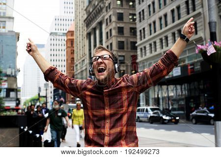 Young man in headphones is happy on the street