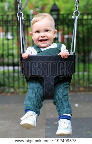 Little boy in overalls on the swing in the Park