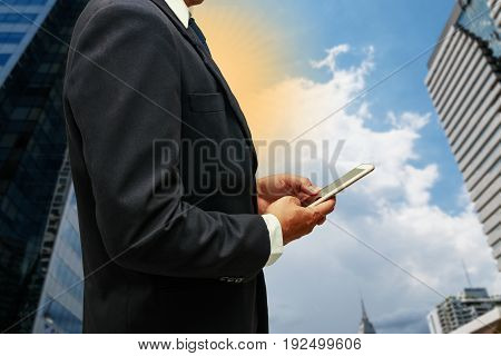 New Businessman using smartphone of cityscape of Bangkok city with sun